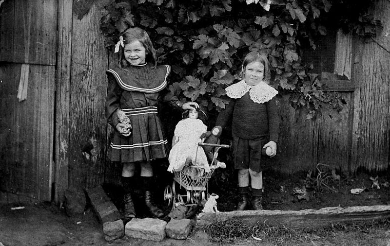 Portrait of two children with dolls in a garden