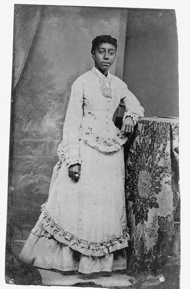 Young African American woman, standing with one arm resting on a table